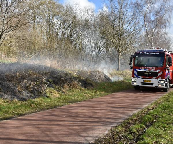 Brandweer blust bermbrand langs fietspad in de wijk Skoatterwâld