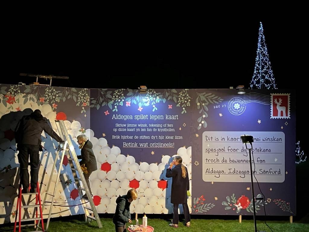 Terwijl vrijwilligers Anko Baarda en Jacob van der Meer de verlichting nog afwerken worden de eerste kerstballen al gevuld op de Kerstkaart XXL op het evenemententerrein in Oudega SWF.